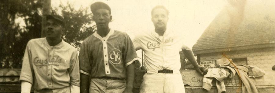 Three baseball players lean against a fence